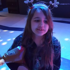 smiling-child-with-long-hair-wearing-reindeer-antlers