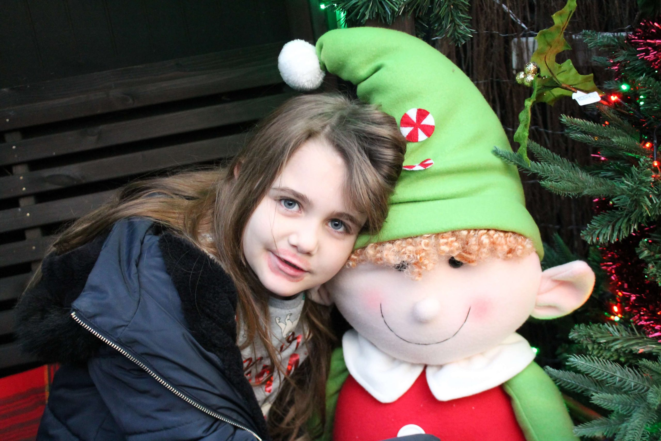 7 year old girl with long brown hair wearing a coat, cuddled up to a cuddly elf with ginger hair and a green pointy hat