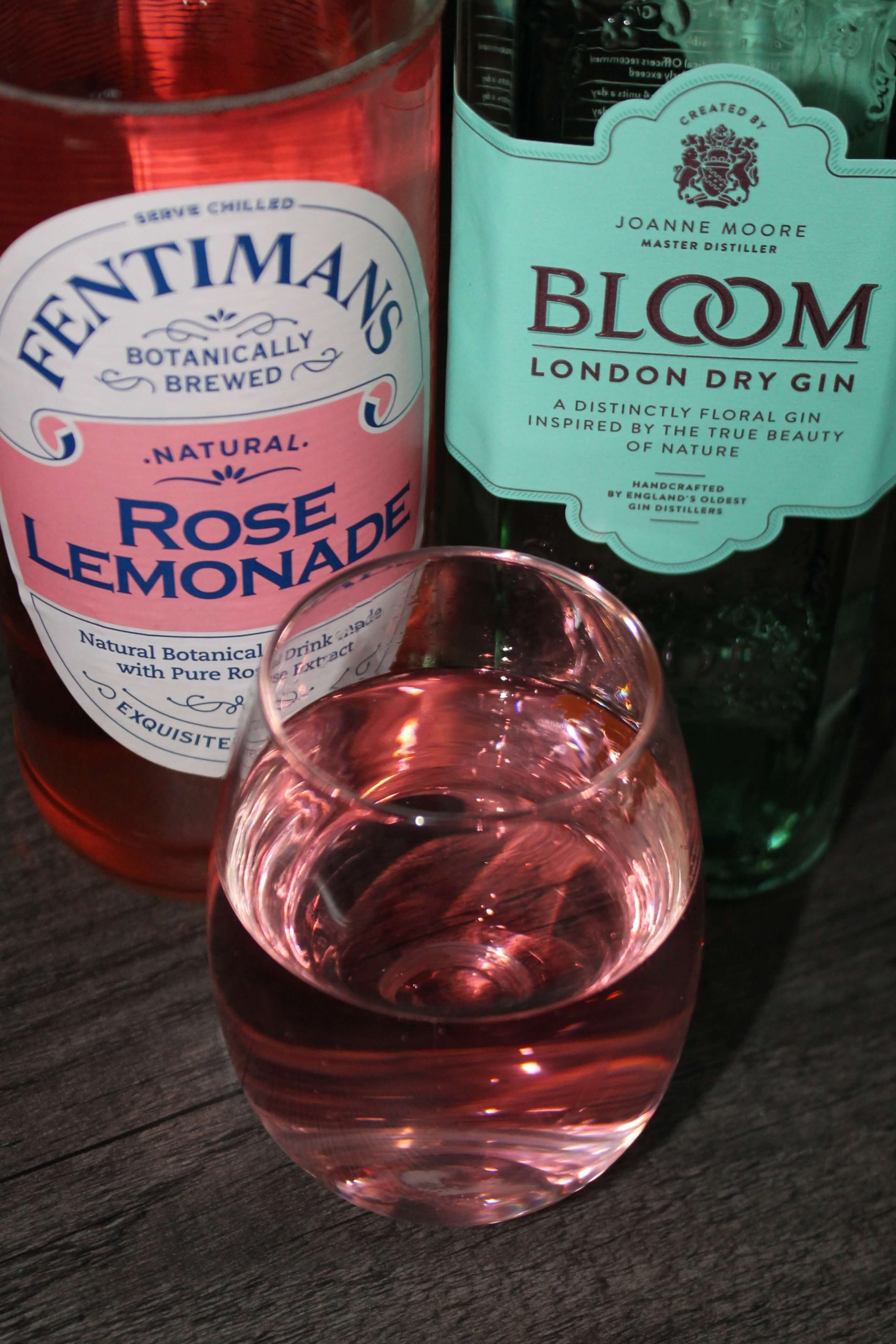 a bottle of fentimans rose lemonade, a bottle of bloom gin and a glass with them in